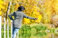一个帽子的女孩有叶子的在站立在船坞的手上 晴朗 回到视图 免版税库存照片