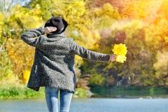 一个帽子的女孩有叶子的在站立在船坞的手上 秋天,晴朗 回到视图 库存图片
