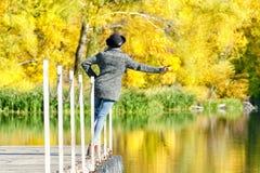 一个帽子的女孩有叶子的在站立在船坞的手上 秋天,晴朗 图库摄影