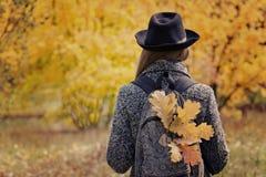 一个帽子的女孩有在背包的黄色叶子的在秋天森林后面视图站立 免版税库存图片