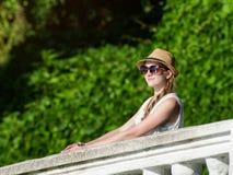 一个帽子的女孩有太阳镜的享受自然的 晴天,公园 图库摄影