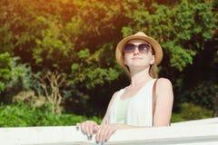 一个帽子的女孩有太阳镜的享受自然的 晴天,公园 库存照片