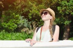 一个帽子的女孩有太阳镜的享受自然的 晴天,公园 免版税库存照片