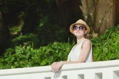 一个帽子的女孩有太阳镜的享受自然的 晴天,公园 免版税库存图片