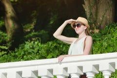 一个帽子的女孩有看对距离的太阳镜的 晴朗的日 库存图片