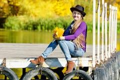 一个帽子的女孩有秋叶花束的坐船坞由河 秋天,晴朗 库存图片