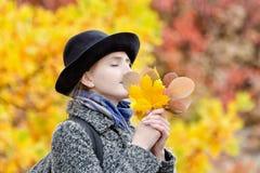 一个帽子的女孩有秋叶花束的  免版税库存照片
