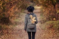 一个帽子的女孩有背包的在秋天森林里站立 免版税库存照片