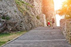 一个帽子的女孩有走在堡垒的墙壁的附近一个年轻儿子的,阳光 回到视图 库存照片
