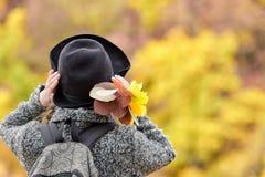 一个帽子的女孩有黄色叶子花束的  秋天森林后面视图 免版税库存照片