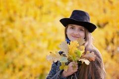 一个帽子的女孩有黄色叶子花束的  秋季森林 库存图片
