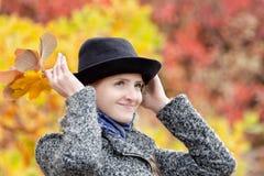 一个帽子的女孩有黄色叶子花束的  秋季森林 免版税库存照片