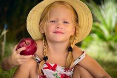 一个帽子的女孩用红色苹果 库存照片