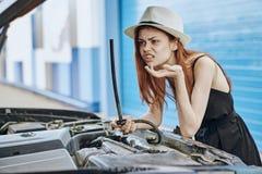 一个帽子的妇女在汽车服务调查汽车,引擎,电池的敞篷 免版税库存图片