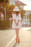 一个帽子的孤独的妇女在一条空的路 图库摄影