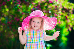 一个帽子的小女孩在开花的夏天庭院里 库存照片