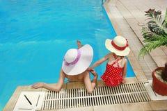 一个帽子的小女孩有游泳池的母亲的 图库摄影