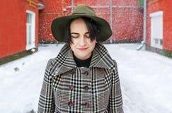 一个帽子的少妇在一个冬天城市红色法院围场 库存照片