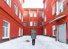 一个帽子的少妇在一个冬天城市红色法院围场 图库摄影