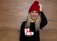 一个帽子的少妇有小的礼物的 美丽的概念礼服女孩纵向佩带的空白冬天 免版税库存图片