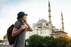 一个帽子的年轻美丽的女孩旅客有背包的谈话在一个手机在蓝色清真寺-著名附近 免版税库存图片