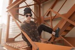 一个帽子的年轻英俊的行家人在牛仔裤的一件军用衬衣在太阳镜的运动鞋坐铁楼梯 库存照片