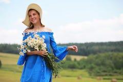一个帽子的年轻逗人喜爱的女孩在日落的一个领域 免版税图库摄影