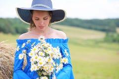 一个帽子的年轻逗人喜爱的女孩在日落的一个领域 库存照片