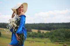 一个帽子的年轻逗人喜爱的女孩在日落的一个领域 图库摄影