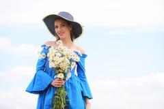 一个帽子的年轻逗人喜爱的女孩在日落的一个领域 库存图片