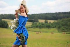 一个帽子的年轻逗人喜爱的女孩在日落的一个领域 免版税库存图片