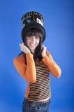 一个帽子的快乐的女孩在蓝色背景 免版税库存照片