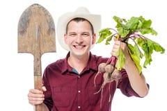 一个帽子的愉快的年轻农夫有在白色的一片甜菜庄稼的 图库摄影