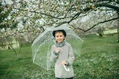 一个帽子的男孩有伞的 免版税库存图片