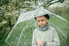 一个帽子的男孩有伞的 免版税库存照片