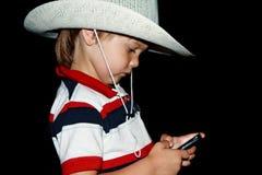 一个帽子的男孩有电话的 免版税库存图片