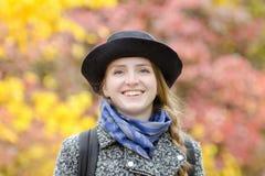 一个帽子的笑的女孩在秋天停放 在背景的明亮的叶子 画象 免版税库存图片