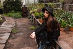 一个帽子的美丽的女孩在植物园的背景 免版税库存图片