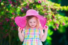 一个帽子的美丽的小女孩在开花的夏天庭院里 免版税库存照片
