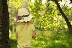 一个帽子的美丽的小女孩在自然 库存照片