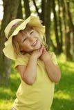 一个帽子的美丽的小女孩在自然 免版税库存图片