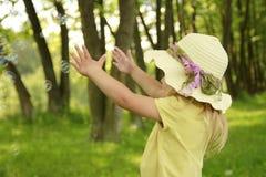 一个帽子的美丽的小女孩在自然 免版税图库摄影