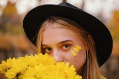 一个帽子的美丽的白肤金发的女孩有黄色花花束的在充分秋天公园黄色叶子 免版税库存照片