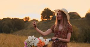 一个帽子的美丽的金发碧眼的女人有看流动手机屏幕和一个篮子在把手的自行车的有花的 影视素材