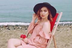 一个帽子的美女有桃红色说谎在懒人的头发和美好的构成的反对海滩和海洋 库存图片