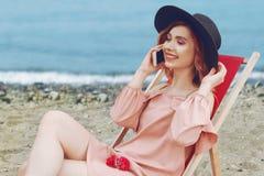 一个帽子的美女有桃红色说谎在懒人的头发和美好的构成的反对海滩和海洋 免版税库存照片