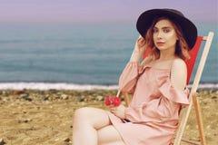 一个帽子的美女有桃红色说谎在懒人的头发和美好的构成的反对海滩和海洋 库存照片