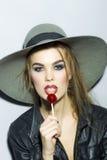 一个帽子的年轻性感的女孩有棒棒糖的 免版税库存图片