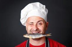 一个帽子的滑稽的厨师有在他的牙的一条干燥鱼的 免版税库存图片