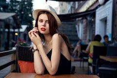 一个帽子的年轻美丽的妇女在一条街道上的一个咖啡馆在一个城市在夏天 免版税库存照片